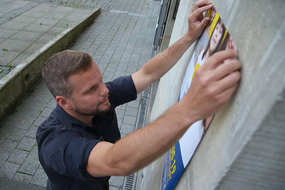 Michael Specht (34) bringt in der Stadt ein Plakat für das Chemnitzer Bürgerfest an.