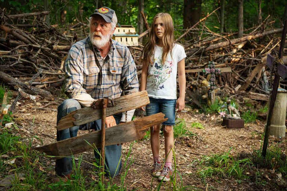 Jud Crandall (l., John Lithgow) schließt die kleine Ellie (Jeté Laurence) ins Herz und warnt sie auch deshalb vor dem Friedhof der Kuscheltiere.