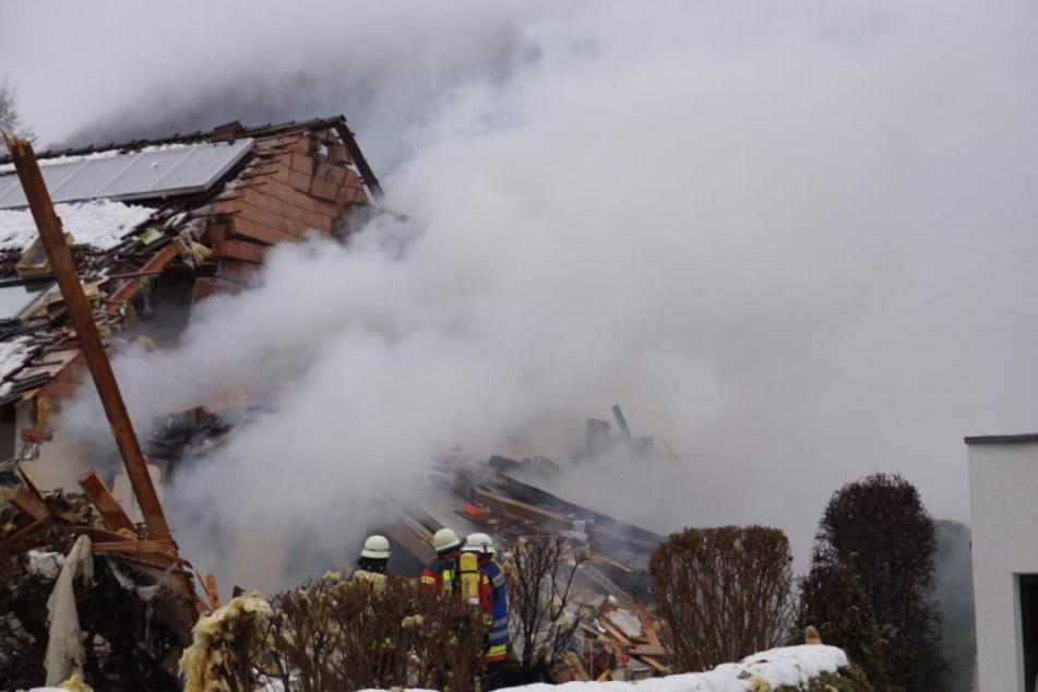 Feuerwehrleute vor dem Haus, das schwer beschädigt wurde.