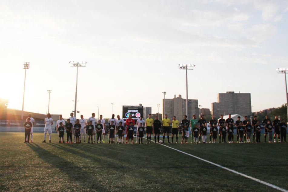 Die Spieler beider Mannschaften - links Cosmos, rechts St. Pauli - stehen im Abendlicht mit Kindern und den Schiedsrichtern auf dem Platz.