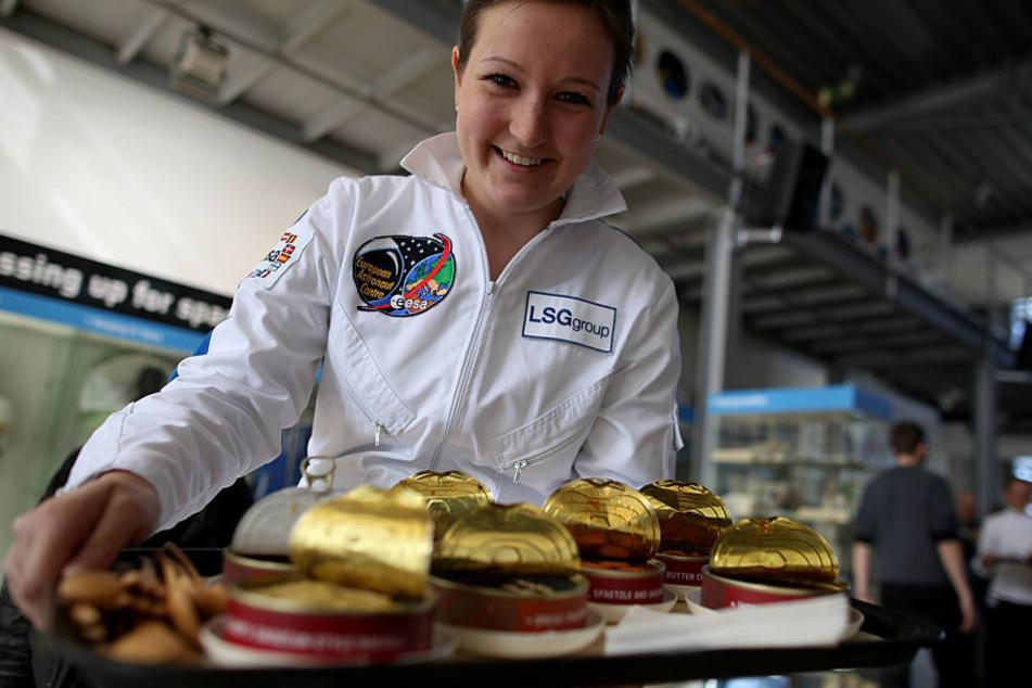 Eine Mitarbeiterin zeigt die Auswahl der Weltraum-Gerichte.