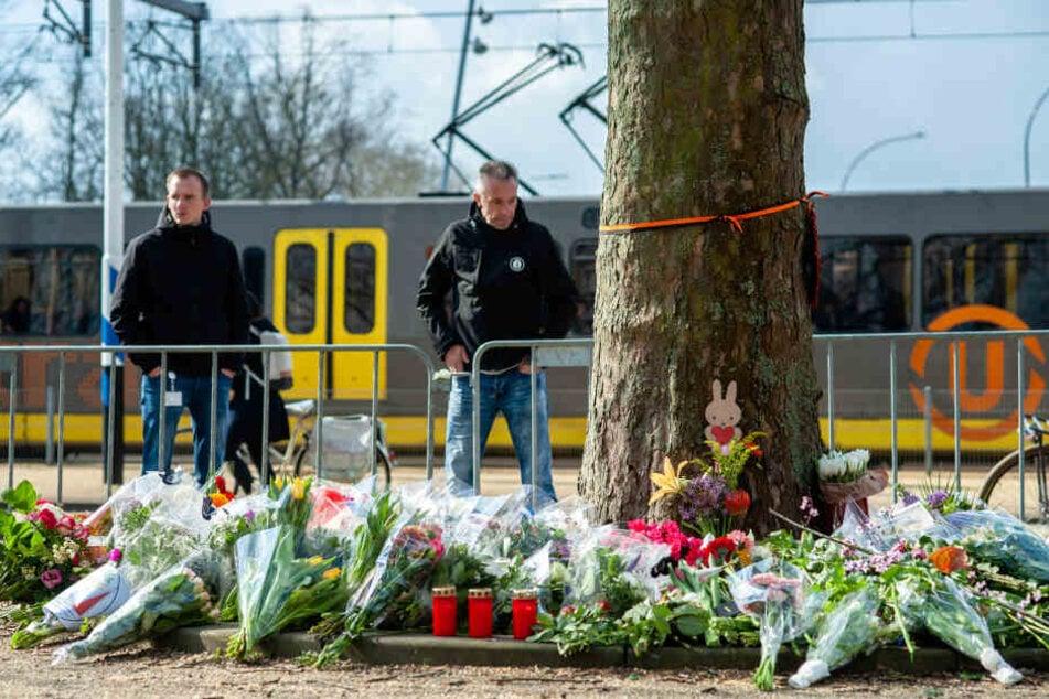 Passanten stehen vor dem provisorischen Denkmal in der Nähe des Ortes, an dem drei Menschen von einem Schützen in einer Straßenbahn getötet wurden.