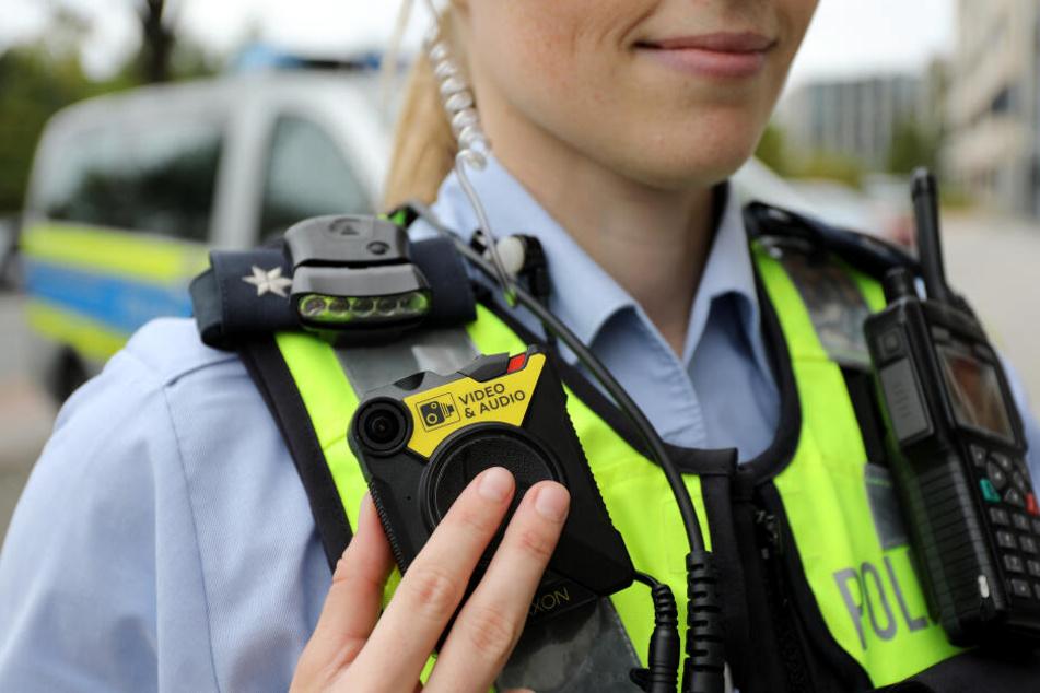 Eine Polizistin der Streifenpolizei führt eine Bodycam vor.