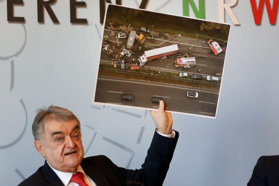 Der nordrhein-westfälische Innenminister Herbert Reul (CDU)zeigt während der Pressekonferenz das Foto eines schweren Verkehrsunfalles mit einem LKW.