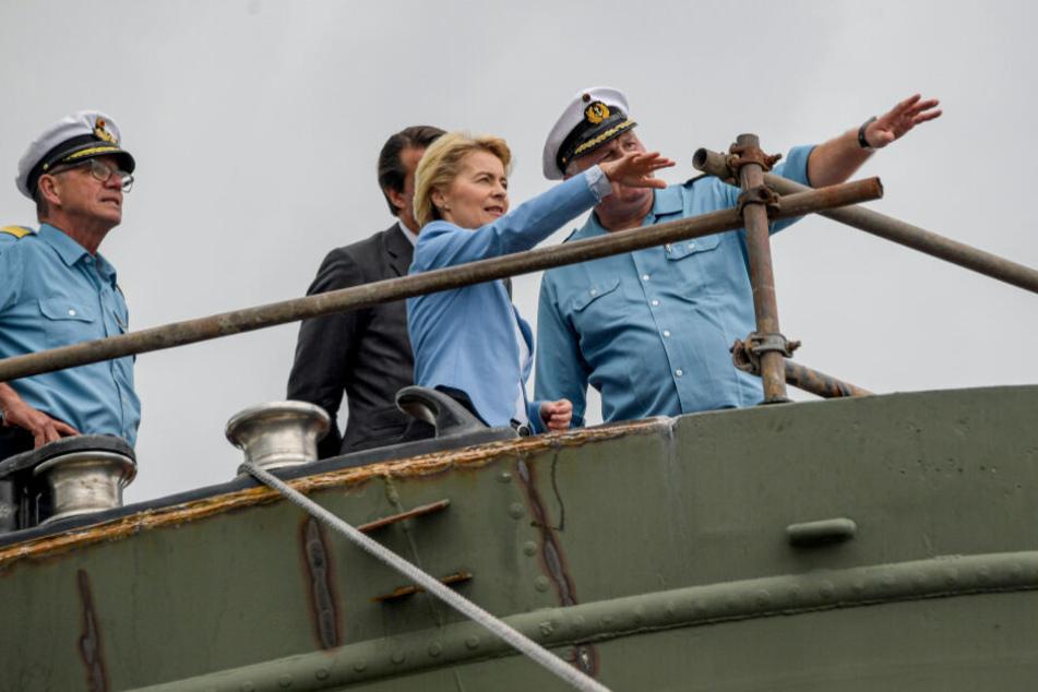 Bundesverteidigungsministerin Ursula von der Leyen steht gemeinsam mit Vize-Admiral Andreas Krause (links) und Nils Brandt (rechts), Kommandant der Gorch Fock, auf dem Segel-Schulschiff.