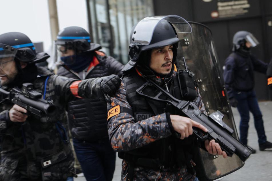 """Bewaffnete Bereitschaftspolizisten beobachten eine Demonstration der """"Gelbwesten""""."""