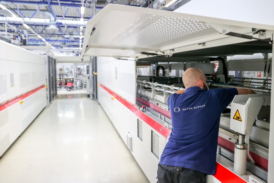 Ein Mitarbeiter richtet die zwölf Meter langen Laminatoren am neuen Sitz des Solarmodul-Herstellers Meyer Burger ein.