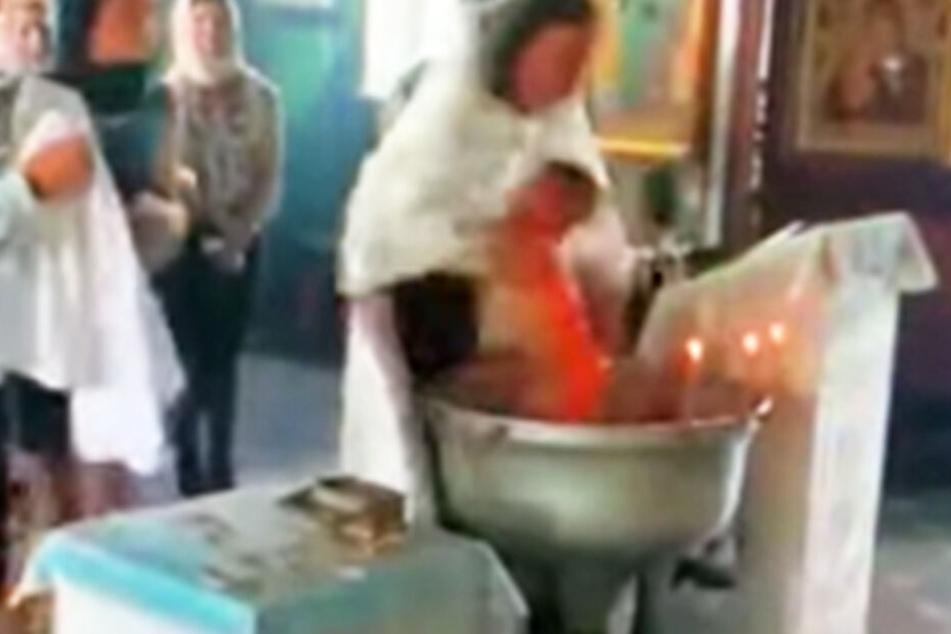Verstörende Bilder! So brutal will ein Priester ein schreiendes Baby taufen