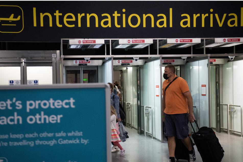"""Passagiere kommen am Flughafen Gatwick in West Sussex an, an dem ein Schild mit der Aufschrift """"Let's protect each other"""" (Lasst uns aufeinander aufpassen) steht."""