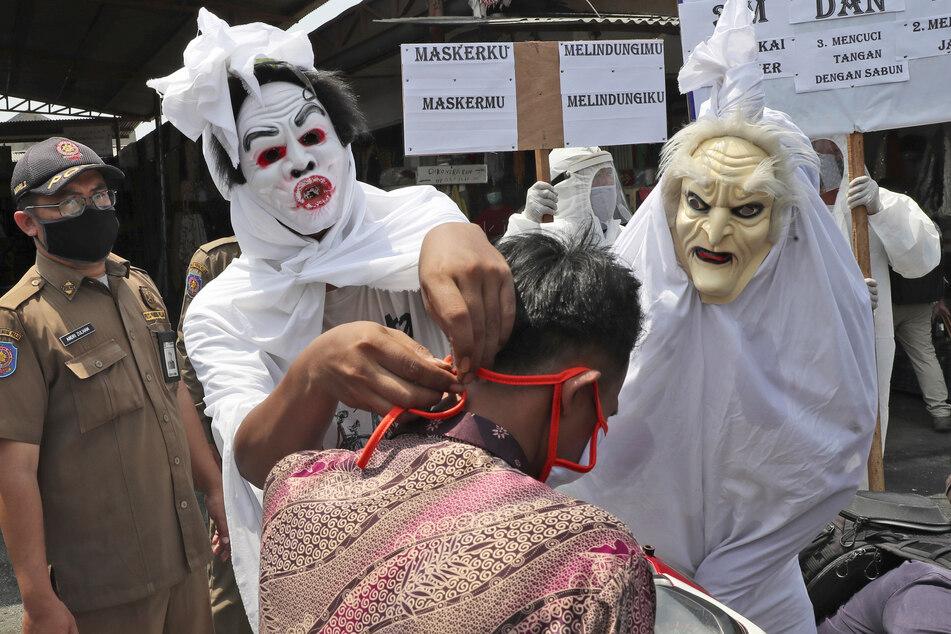 """Mitarbeiter der indonesischen Gesundheitsbehörden, verkleidet als """"Pocong""""-Geister, klären Passanten über die Corona-Maskenpflicht und Abstandsregeln auf."""