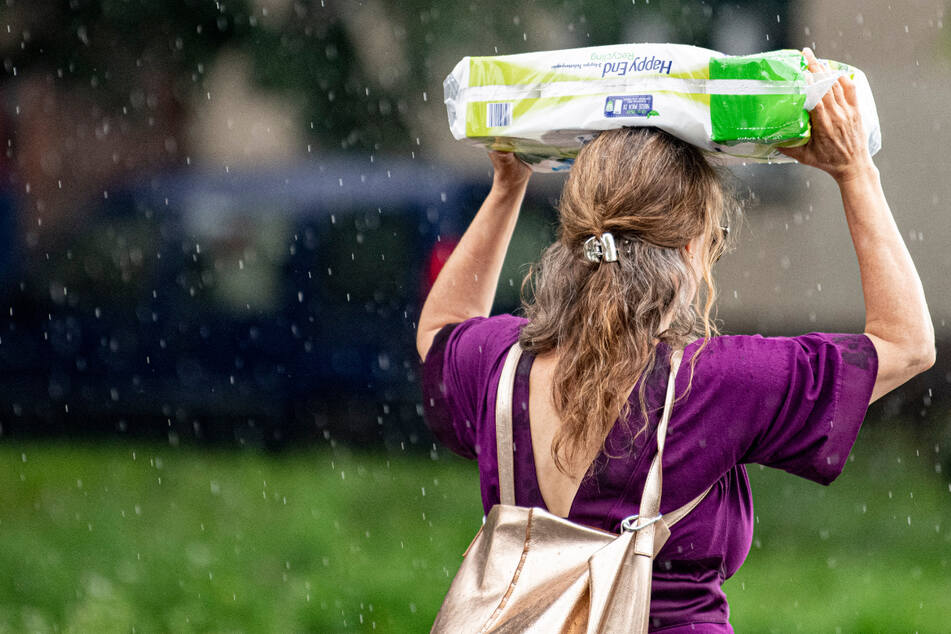 Eine Berlinerin schützt sich vor dem starken Regenfall mit einer Packung Klopapier. Auch am Freitag ist wieder mit Starkregen zu rechnen.