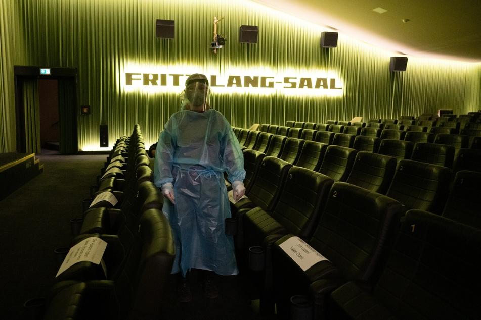 Eine Mitarbeiterin verteilt in einem Kinosaal, der als Wartebereich dient, in einem Corona-Schnelltest-Zentrum im Filmtheater Schauburg die Testergebnisse. Das Kino bietet in seinem Foyer einen Antigen-Schnelltest an.