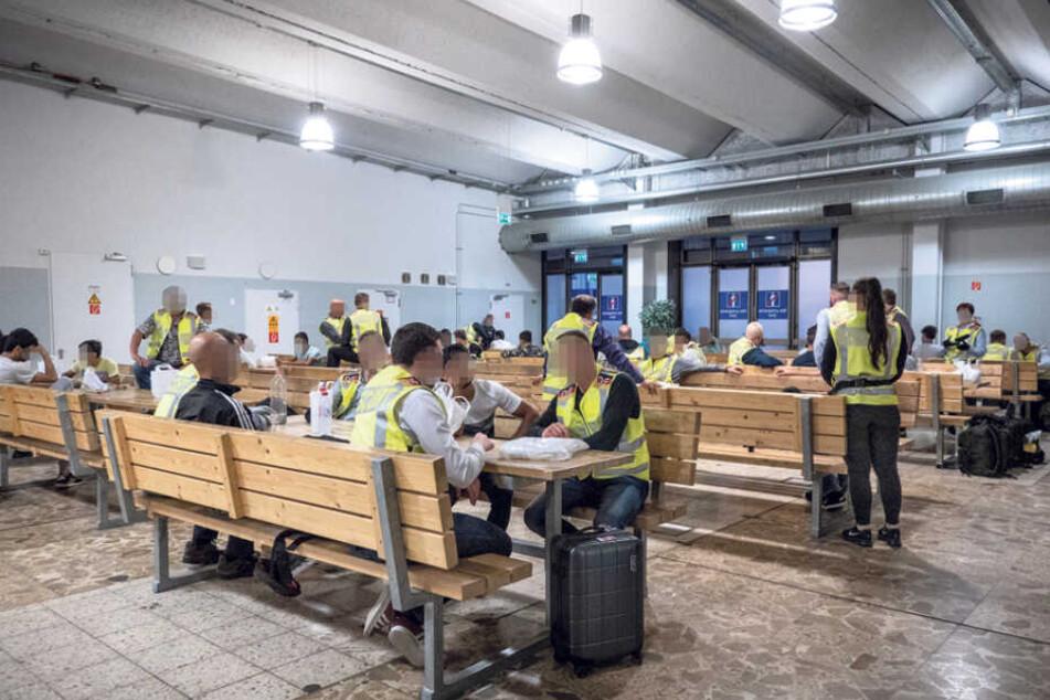 Polizisten warten mit Ausreisepflichtigen auf dem Flughafen Leipzig in einer Abflughalle. Tische und Bänke wurden besonders massiv ausgeführt, um mögliches Randalieren zu vermeiden.