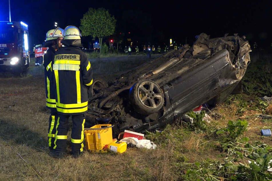 Das Wrack des Autos wird von Feuerwehrmännern begutachtet.