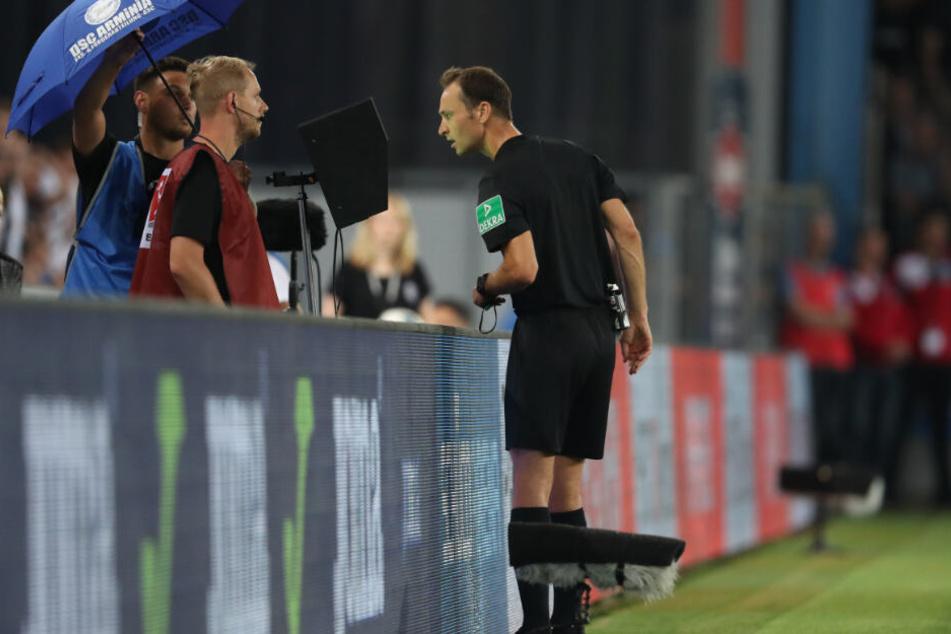 Schiedsrichter Bastian Dankert schaut sich eine strittige Szene selbst am Bildschirm an.