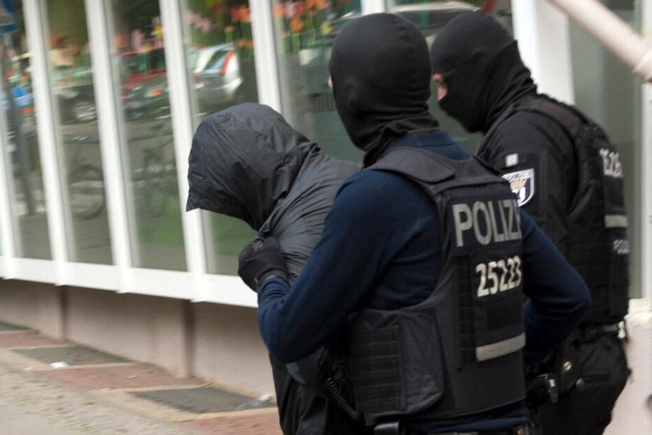 Polizisten führen einen der Verdächtigen des Gold-Münzen-Raubes ab.