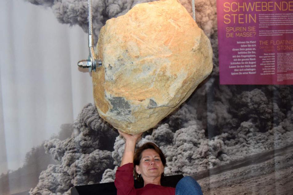"""Eine Mitarbeiterin der Gesellschaft für Tourismus und Stadtmarketing Schotten liegt unter dem """"Hängenden Stein"""" im Erlebnismuseum."""