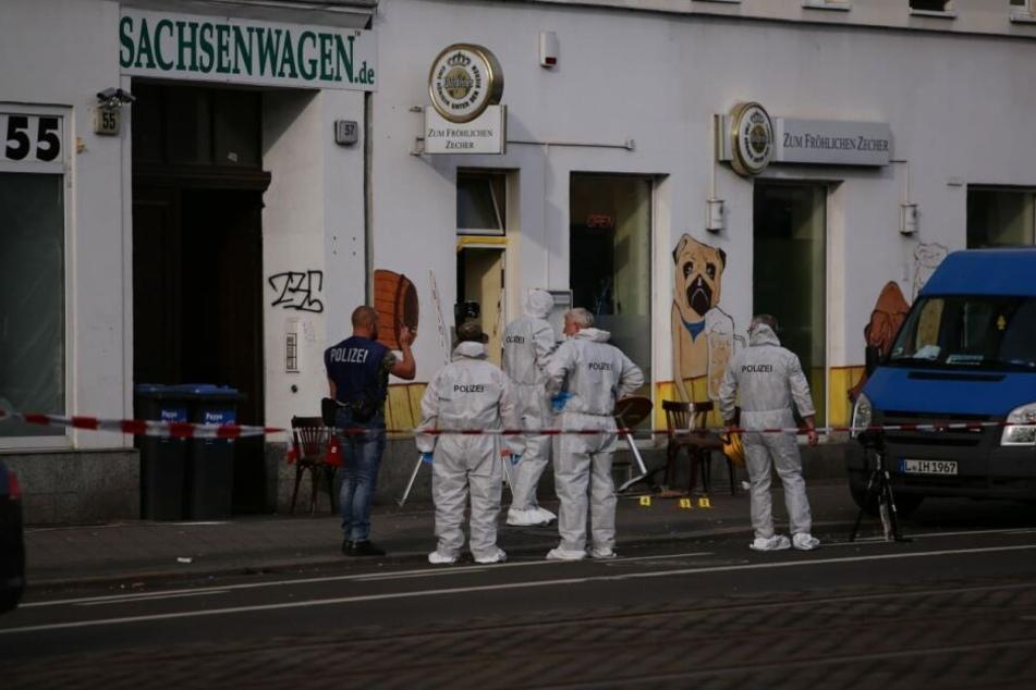 Beamte der Tatortgruppe sichern vor dem Lokal Spuren, darunter mehrere Patronenhülsen.