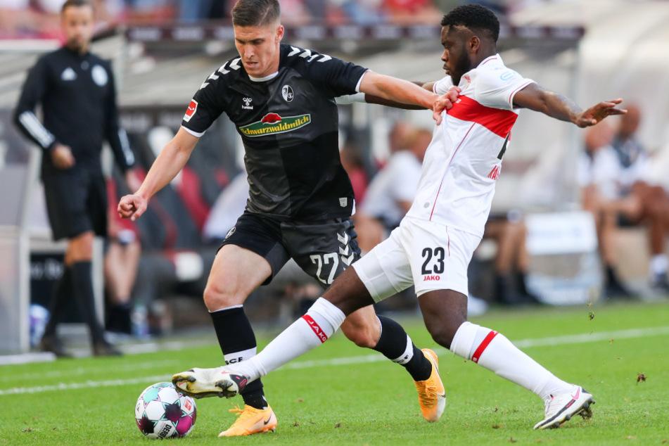 Freiburgs Roland Sallai (l, 23) und Stuttgarts Orel Mangala (22) kämpfen um den Ball.