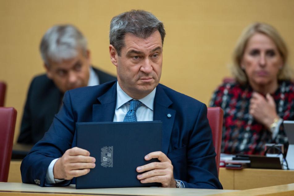 Markus Söder (CSU), Ministerpräsident von Bayern, hält die Regierungserklärung bei der Plenarsitzung im bayerischen Landtag in den Händen.