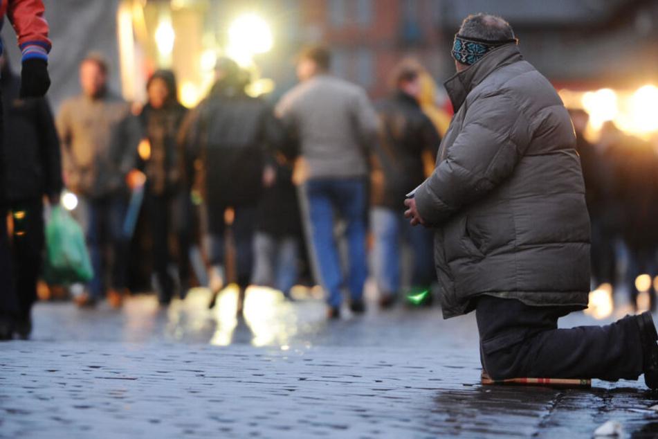 Ein Bettler kniet auf dem Boden. (Symbolbild)