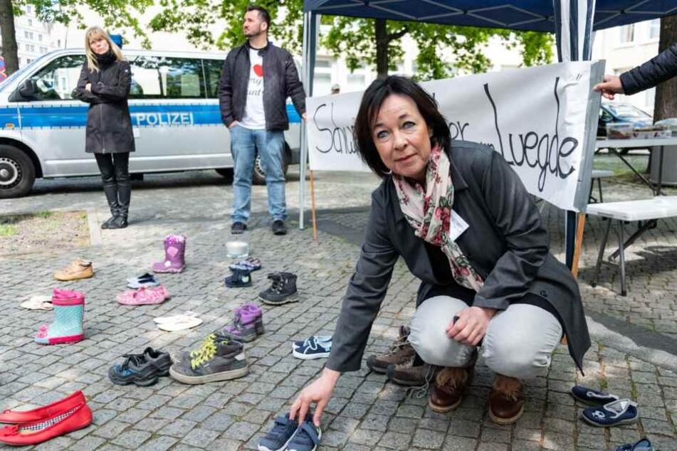 """Sprecherin der Initiative """"Kinder von Lügde"""", Ina Tolksdorf, verteilt vor dem Landtag in Hannover Kinderschuhe."""