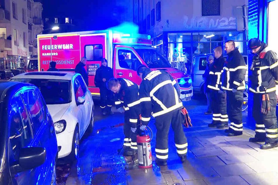 Feuerwehrleute entfernen das Blut von der Straße, während im Rettungswagen ein Verletzter versorgt wird.