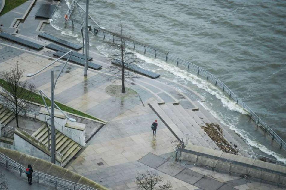 Fußgänger gehen bei Sturm und Regen durch die Hamburger Hafencity
