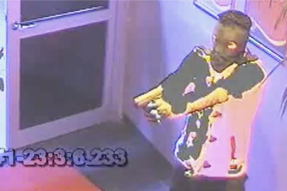 Der Screenshot zeigt, wie einer der beiden Räuber mit der Pistole in der Hand drohend dasteht