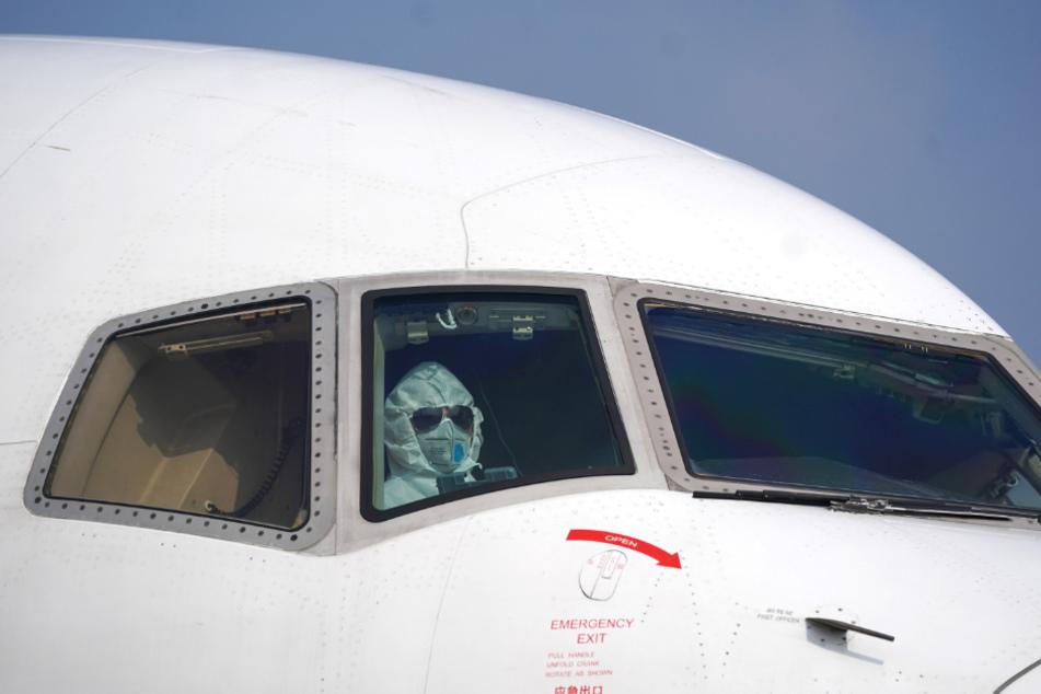 Ein Pilot sitzt mit Schutzanzug und Maske im Cockpit und parkt ein Flugzeug auf dem Internationalen Flughafen Wuhan-Tianhe.