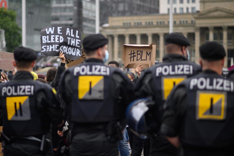 Polizeibeamte stehen während einer Demonstration gegen Rassismus vor Demonstranten in Stuttgart.