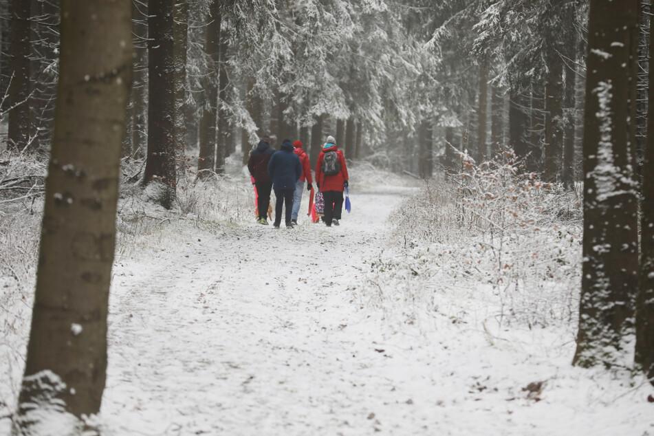 Wanderer laufen entlang des Rennsteiges durch den schneebedeckten Thüringer Wald. Auch an diesem Wochenende hat es wieder zahlreiche Menschen in die Winterlandschaften des Freistaates gelockt. (Archivbild)