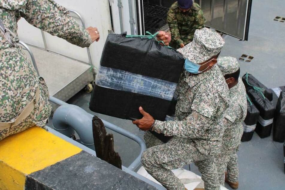 Soldaten entladen die beschlagnahmte Drogen aus dem Halbtaucher.