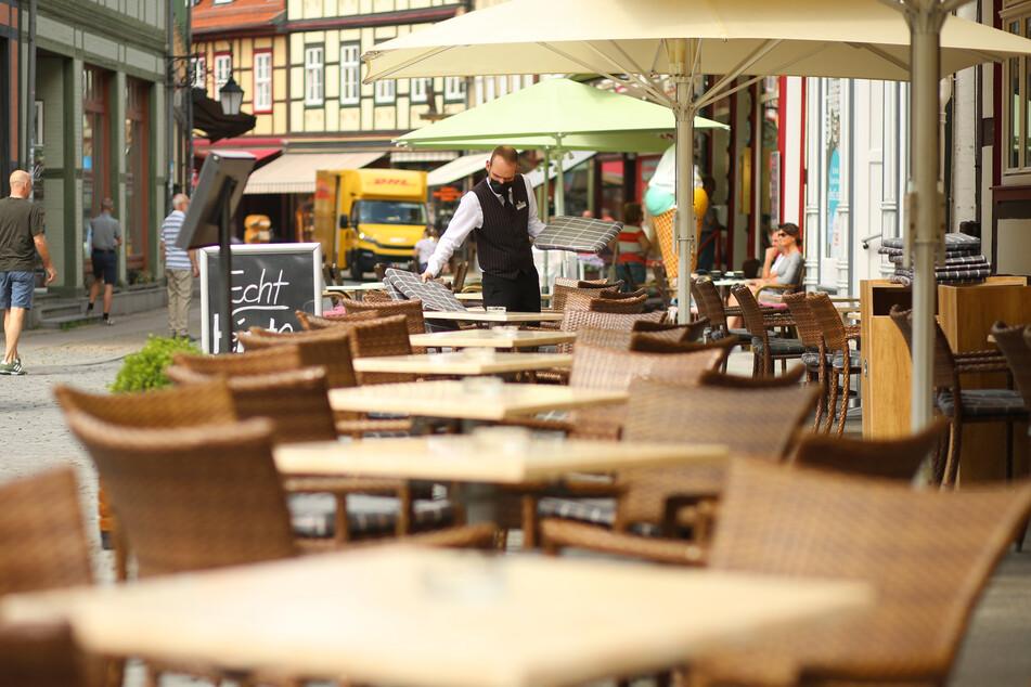 Sachsen-Anhalt, Wernigerode: Ein Kellner deckt die Tische des Außenbereichs eines Hotels ein. Nach langer Zwangspause mit Insolvenzsorgen können Lokale, Hotels und Touristikbetriebe endlich in die Sommersaison starten.