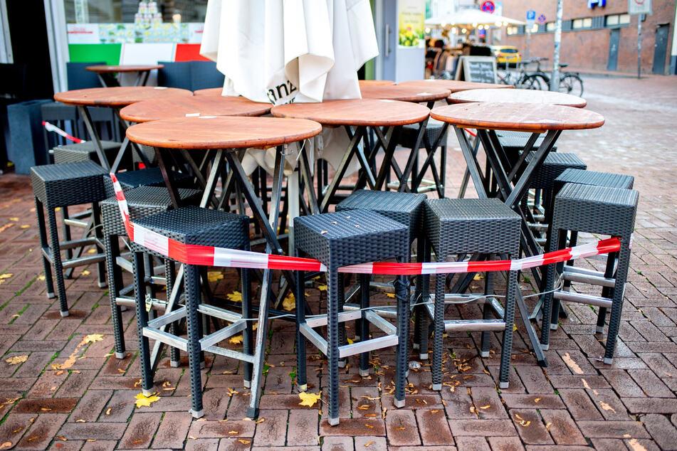 Tische und Stühle stehen vor einer Pizzeria.