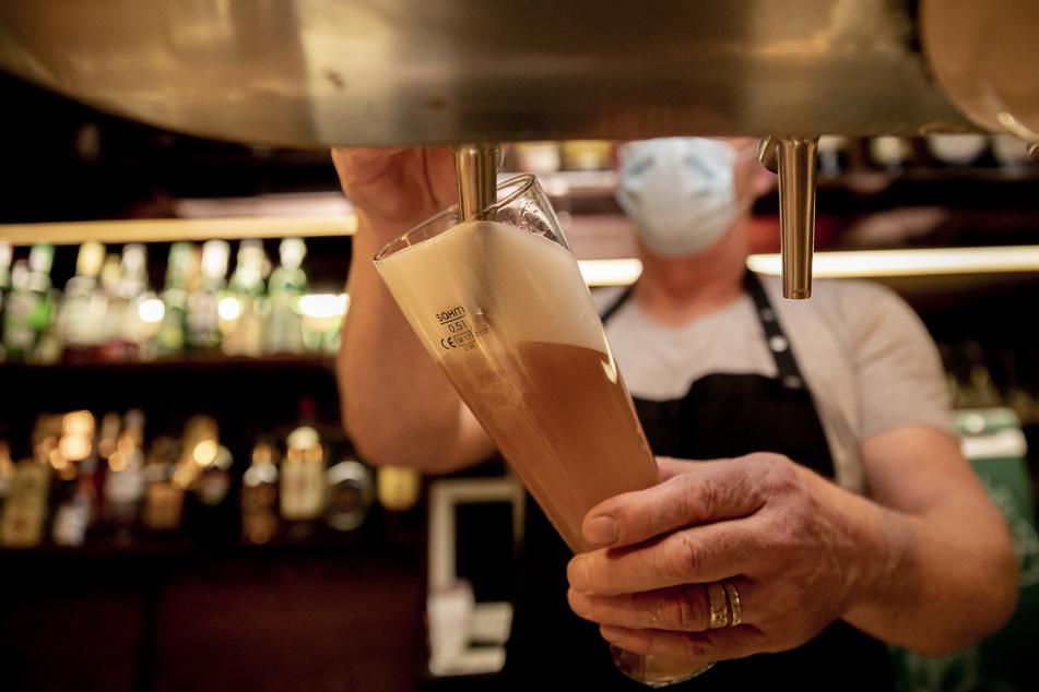 Ein Wirt mit Maske zapft in einer Kneipe Bier.