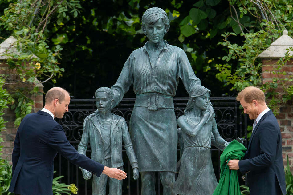 Prince William (l.) and Prince Harry (r.) look happy to be together as they unveil the statue of their mother that has been in the works for five years.