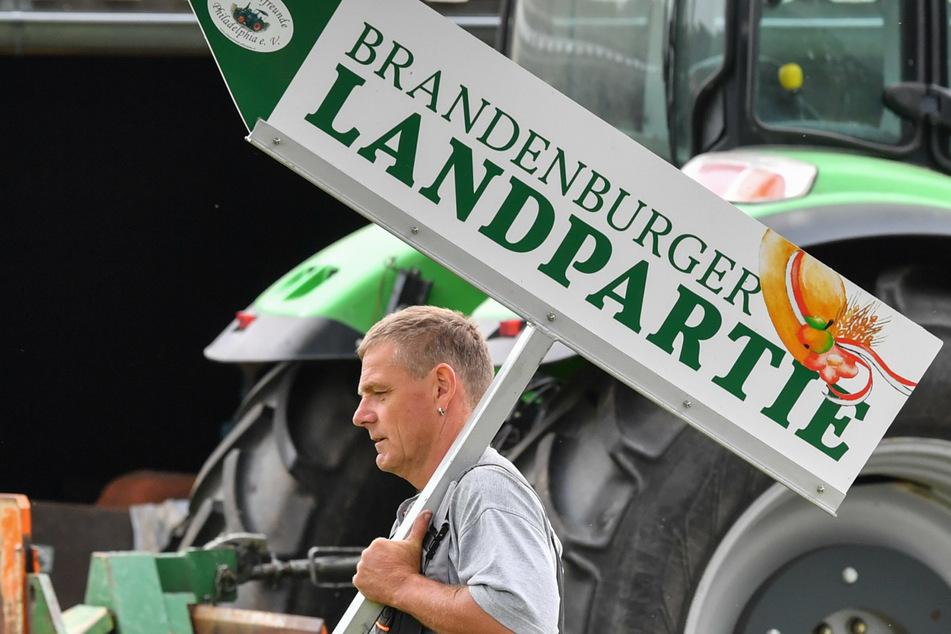 """Trecker-Fan Ralf Wittke trägt im Juni 2018 ein Schild mit der Aufschrift """"Brandenburger Landpartie"""", über seinen Hof. (Archivbild)"""