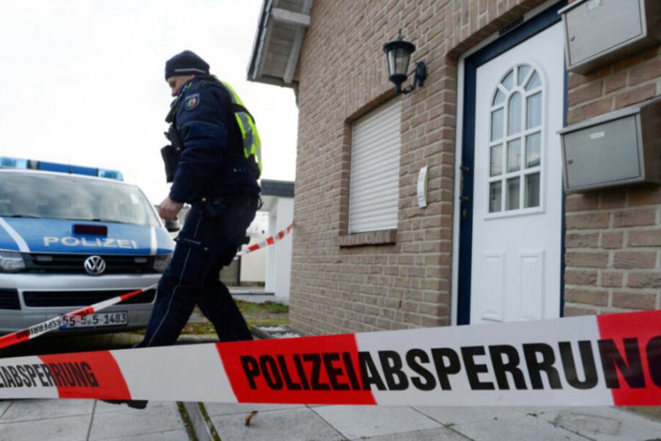 Ein Polizist verlässt ein Haus. (Symbolbild)