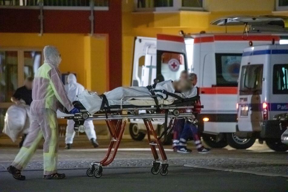 Eine mit Corona infizierte Bewohnerin der K&S Seniorenresidenz wird von Sanitätern in Schutzanzügen evakuiert.