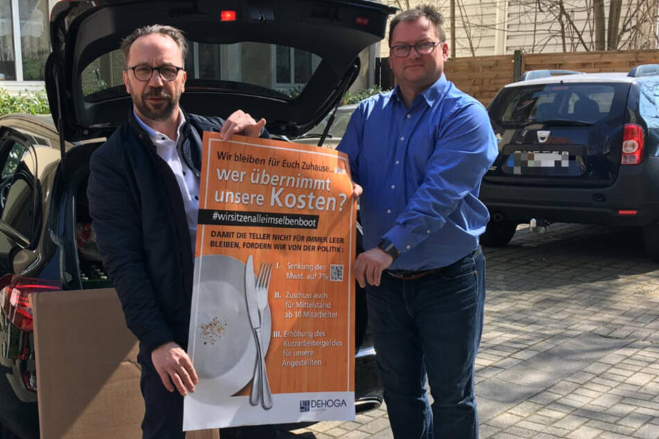 Detlef Knaack (l.), Vorstandsmitglied der DEHOGA Sachsen, bei der Übergabe der Plakate an Axel Klein, Hauptgeschäftsführer der DEHOGA Sachsen in Dresden.