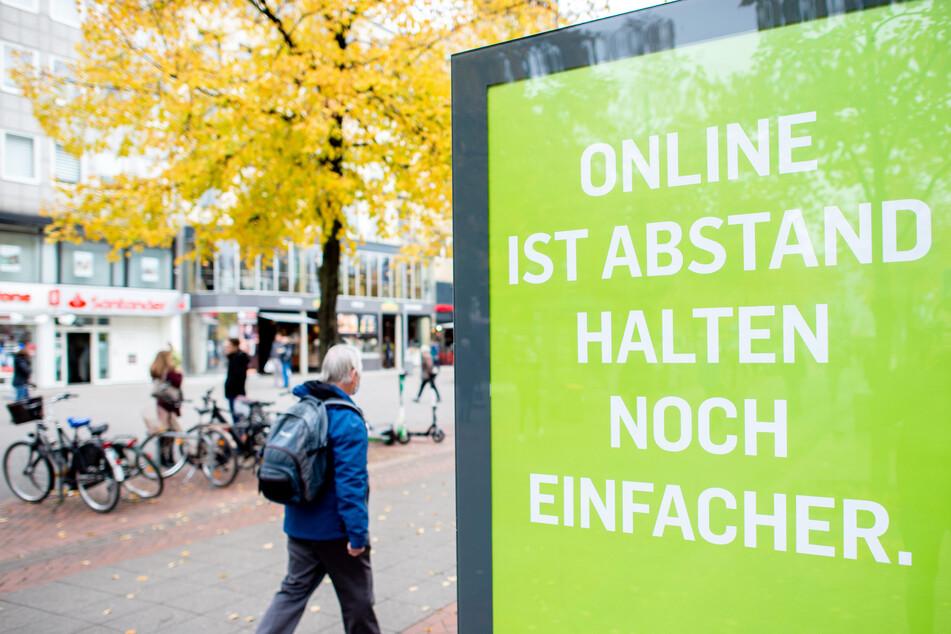 """Ein Mann geht in der Innenstadt Hannovers an einer Werbetafel mit der Aufschrift """"Online ist Abstand halten noch einfacher"""" vorbei."""