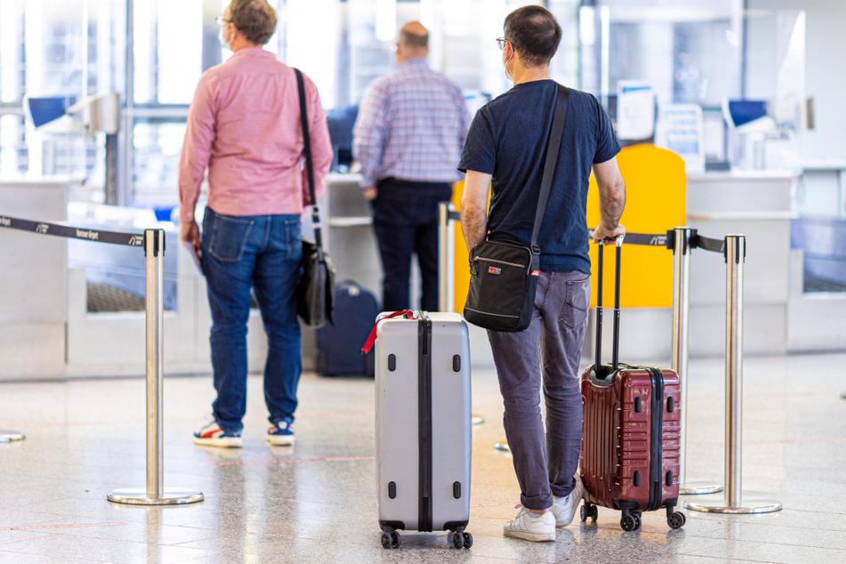 Niedersachsen: Fluggäste stehen im Flughafen Hannover-Langenhagen am Check-in.