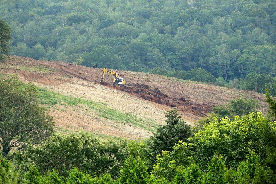 Ein Bagger gräbt während einer Suchaktion der Polizei eine Fläche unweit eines Waldgebiets in der Nähe des Ortes Issancourt-et-Rumel um.