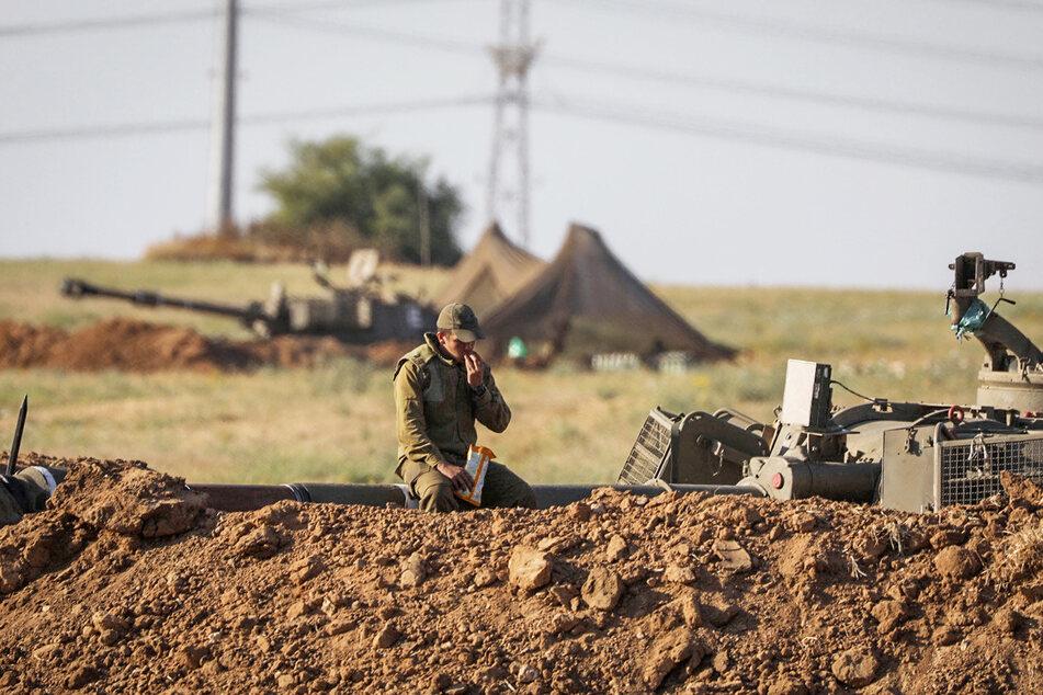 Ein Soldat der Israelischen Verteidigungsstreitkräfte (IDF) ruht sich auf einem Rohr einer Artilleriebatterie aus.