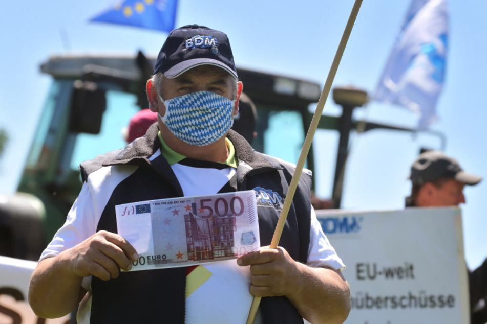 Ein Landwirt hält auf einer Protestaktion des Bundesverbandes der Deutschen Milchviehhalter (BDM) eine symbolische Banknote.