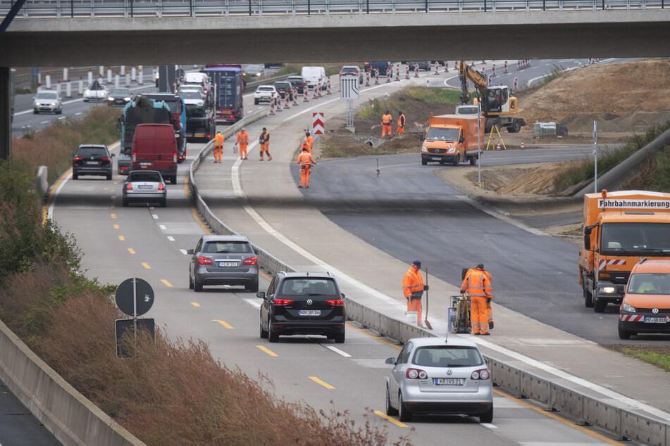 Bauarbeiter stehen in einer Baustelle auf der Autobahn A7.