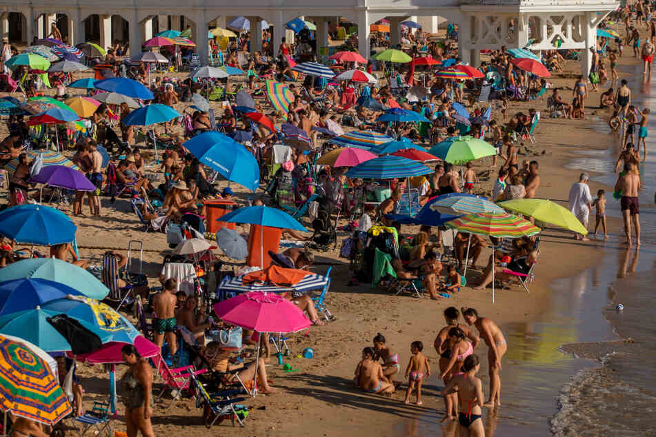 Touristen am gut besuchten Strand in Cadiz. So ein Sommer-Urlaub in Spanien kostet nicht nur Geld, sondern viele Briten nun auch zwei Wochen Quarantäne.