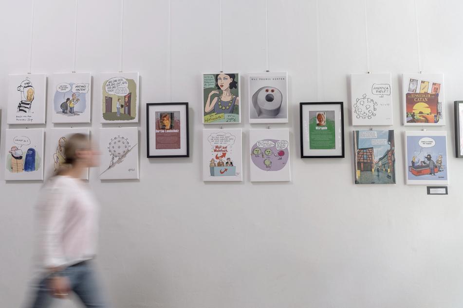"""Eine Frau schaut sich Karikaturen in der Ausstellung """"Ansteckende Cartoons"""" an."""