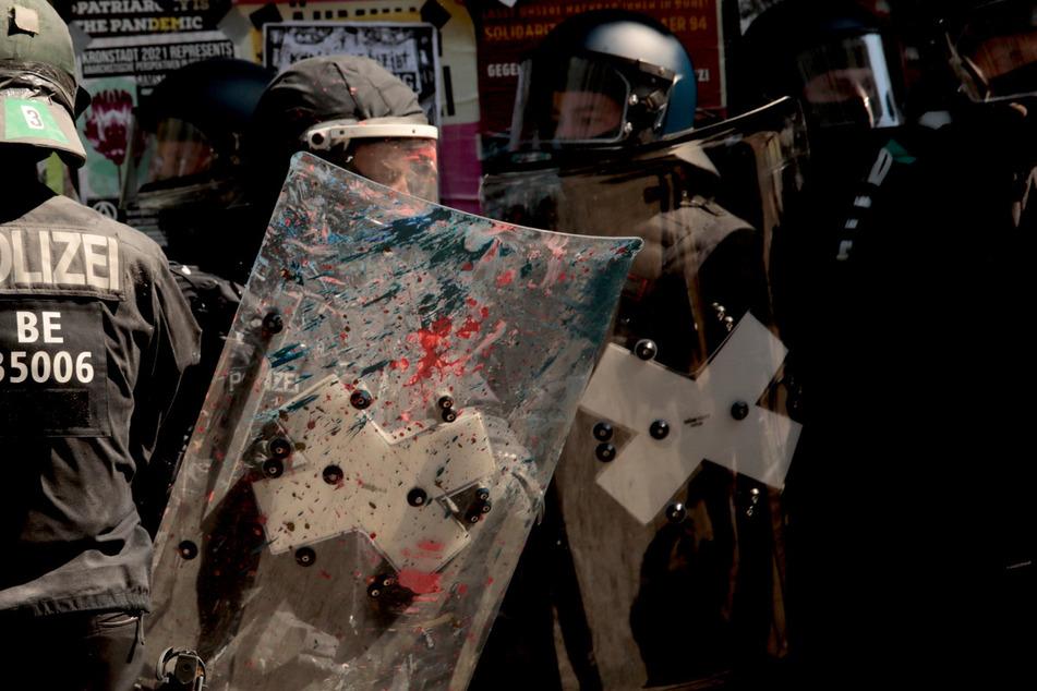 Polizisten haben Kalk und Farbe auf den Uniformen als sie nach der gewaltsamen Öffnung das Haus Rigaer Straße 94 in Berlin-Friedrichshain verlassen.